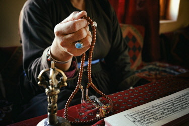 HMS3026593 India, Jammu and Kashmir State, Himalaya, Ladakh, hand of a woman holding a rosary (Buddhist prayer beads) and reading Buddhist texts