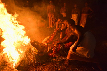 HMS2214630 India, Kerala, Kannur region, Mundiyat Bhagavathi temple, Pottan Theyyam lying and burning on a pyre