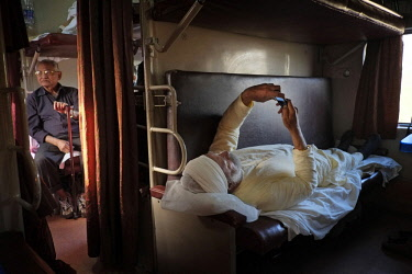 HMS3012122 India, Maharashtra State, Mumbai or Bombay, a Sikh consults his cell phone in a sleeper train arriving in Mumbai,