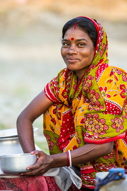 HMS2236377 India, West Bengal, Sundarbans, listed as World Heritage by UNESCO, Mazidbari village, woman cleaning her dishes at the edge ot the path