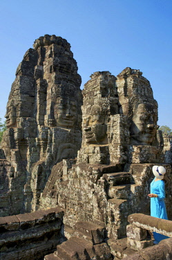 HMS3199529 Cambodia, Angkor, listed as World Heritage by UNESCO, woamn dressed with blue dress and hat in the middle of the carved heads of Bodhisattva composing the Bayon, the main temple of the old khmer town...