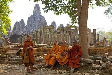 HMS3199533 Cambodia, Angkor, listed as World Heritage by UNESCO, buddists monks dressed in saffron robes discussing in front of the Bayon, the main temple of the old khmer town of Angkor Thom