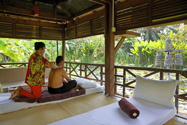 HMS3199559 Cambodia, Battambang, man getting massaged back in Maisons Wat Kor hotel pavilion overlooking a pond with water lilies