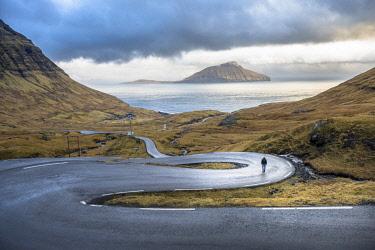 AURSAPA001146 Distant view of man walking on winding road on seashore, Faroe Islands, Denmark