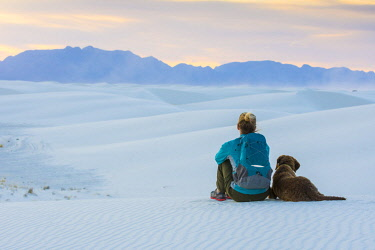 AURHAKE001392 Rear view of woman and dog sitting while hiking in White Sands National Monument, Alamogordo, New Mexico, USA