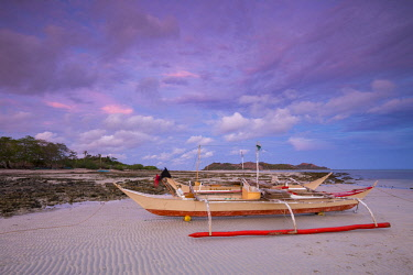 HMS3082548 Philippines, Palawan, Dumaran Island, traditional fishing boat at sunset on Araceli beach