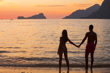 HMS3145868 Philippines, Palawan, El Nido, couple watching the sunset on Las Cabañas Beach