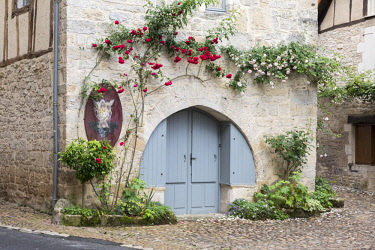FRA10458AW Europe, Midi-Pyrenees, Correze France,  Dordogne Valley, Martel, facade of a medieval building with roses above the doorway
