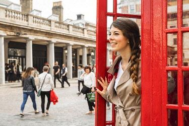 CLKNM90672 Woman posing in Phone Box, Covent Garden, London, United Kingdom (MR)