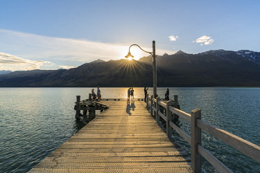 CLKFV90067 People on the jetty on Lake Wakatipu just before sunset. Glenorchy, Queenstown Lakes district, Otago region, South Island, New Zealand.