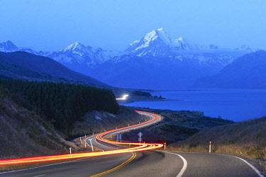 CLKFV91096 Car lights at dusk, looking towards Mt Cook NP mountain range. Ben Ohau, Mackenzie district, Canterbury region, South Island, New Zealand.
