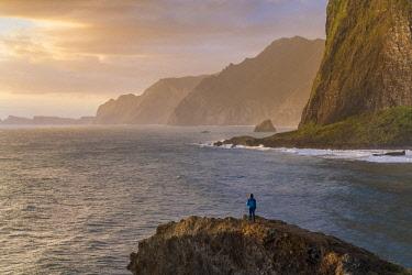 CLKFV91618 Woman on a cliff watching the sunrise. Faial, Santana municipality, Madeira Island, Portugal. (MR)