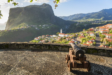 CLKFV91628 Historical cannon at Faial fortress with the village in the background. Faial, Santana municipality, Madeira Island, Portugal.