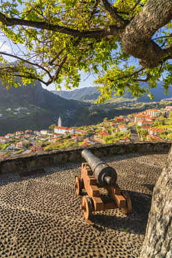CLKFV91629 Historical cannon at Faial fortress with the village in the background. Faial, Santana municipality, Madeira Island, Portugal.