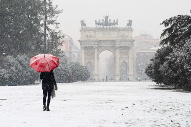 CLKAC90872 A woman with red umbrella walks in Sempione park during a snowfall. Milan, Lombardy, Italy (MR)