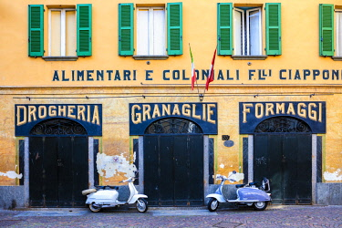 CLKRM91114 Couple of Lambretta Innocenti scooter parked at the old grocery, Morbegno, province of Sondrio, Valtellina, Lombardy, Italy