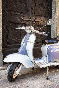 CLKRM91115 Bicolored Lambretta Innocenti scooter in front of ancient doorway, Morbegno, Sondrio province, Valtellina, Lombardy, Italy