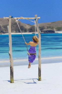 ARTRKO020273 Rear view of woman in purple dress on swing on beach, Kuta, Lombok, Indonesia