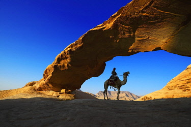 IBXNEX04576326 Bedouin rides his camel, Rock-Arch Al Kharza, Wadi Rum, Jordan, Asia