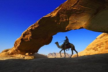 IBXNEX04576327 Bedouin rides his camel, Rock-Arch Al Kharza, Wadi Rum, Jordan, Asia