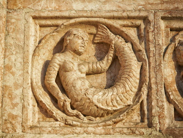 IBXPWP04354729 Medieval relief sculpture of mythical mermaid on the exterior of the Romanesque Baptistery, Parma, Emilia Romagna, Italy, Europe