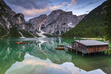 IBXSEI04718782 Green mountain lake with boats and boathouse, Seekogel peak in the back, water reflection, Lake Prags, Dolomites, Italy, Europe