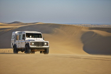 IBXVCH04644620 Off-road vehicle drives over sand dunes at Lange Wand on the Atlantic coast, Namib-Naukluft-Park, Namibia, Africa