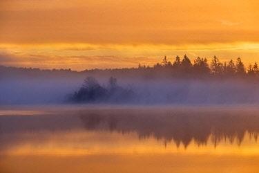 IBXMAN04635322 Dawn, sunrise with early morning mist over Kirchsee, Sachsenkam, Upper Bavaria, Bavaria, Germany, Europe