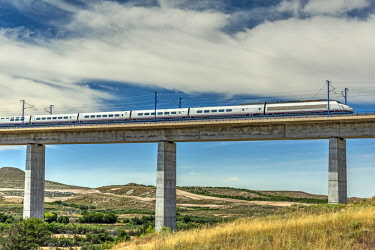 SPA8199AW The Madrid-Barcelona AVE high-speed passenger train while is crossing a viaduct, Fuentes de Ebro, Aragon, Spain