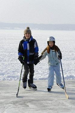 IBLDWB02318037 Girl and boy playing ice hockey, near St. Heinrich, Lake Starnberg, Five Lakes region, Upper Bavaria, Bavaria, Germany, Europe