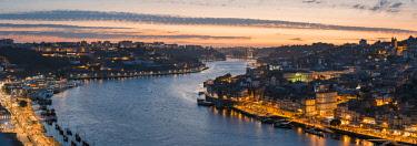 POR9919AWRF Portugal, Norte region, Porto (Oporto). Douro river banks at dusk with Arrabida bridge in the background.