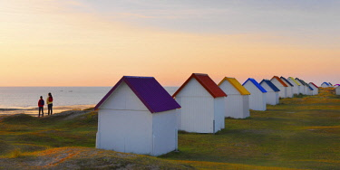 FRA10525AW France, Normandy, Gouville Sur Mer, colourful beach huts, two people standing by sea at dusk (MR)