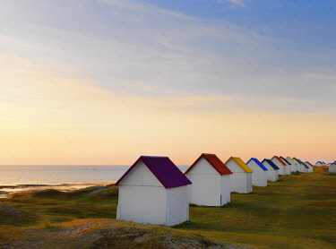 FRA10526AW France, Normandy, Gouville Sur Mer, colourful beach huts at dusk