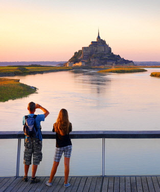 FRA10534AW France, Normandy, Le Mont Saint Michel, boy and girl on bridge at dusk