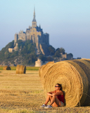 FRA10537AW France, Normandy, Le Mont Saint Michel woman leaning against round hay bail (MR)