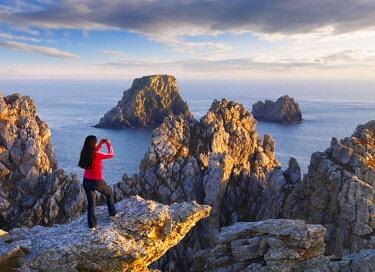 FRA10696AW France, Finistere, Armorica Regional Natural Park, Crozon peninsula, Camaret-sur-Mer, Pointe de Pen-Hir, Tas de Pois, Girl with camera (MR)