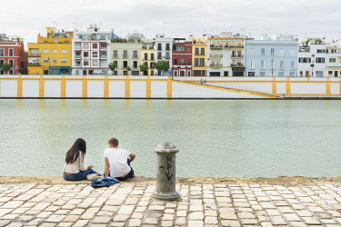 FVG029708 People sitting along the bank of the river Guadalquivir with Triana quarter in the background, Seville, Spain