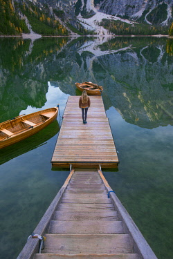 FVG031245 Tourist on the pier of the Braies Lake Dolomites, Pusteria Valley, Italy