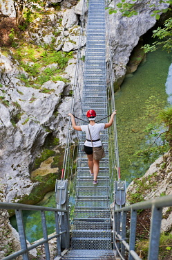 FVG032388 A girl has fun on a suspension bridge in the park of the Friuli Dolomites above the river Cellina, Barcis, Friuli Venezia Giulia, Italy