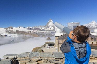 FVG035209 Child in the top of Gornergrat admiring the Matterhorn or Cervino mountain peak with a coin operated binoculars, Zermatt, Valis, Switzerland, Europe
