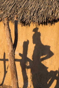 AF31BTH0140 Shadow of a Himba woman on the side of a village hut in a remote village near Opuwo.