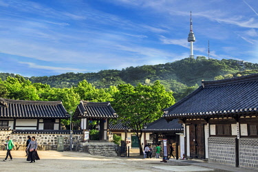 AS18MGL0052 Seoul, South Korea. Traditional Korean village courtyard of Namsangol Hanok with the YTN Seoul Tower (Namsan Tower or Seoul Tower) in the background.