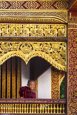 AS36MGL0123 Chiang Mai, Thailand. Wat Pra Singh, Young monk smiles as he studies and prays at temple