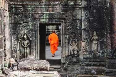 AS40MGL0055 Siem Reap, Cambodia. Monk walks through a doorway among the ancient ruins and towers of the Bayon Temple in Preah Khan