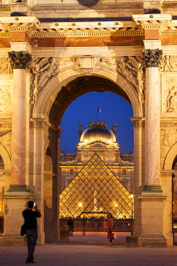 EU09BJN2009 Tourists taking photo of Musee du Louvre viewed through the archway of Arc de Triomphe du Carrousel, Paris France