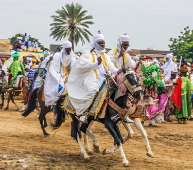 NGR1015 Nigeria, Kano State, Kano. Hausa horsemen gallop through a market in Kano.