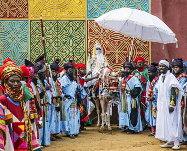 NGR1016 Nigeria, Kano State, Kano. The Emir of Kano mounted on a white horse pauses beside a traditionally decorated wall at his palace with a group of well-dressed followers in attendance.