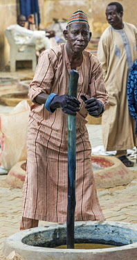NGR1031 Nigeria, Kano State, Kano. A man mixes indigo dye in one of the ancient 500 year-old Kofar Mata dyeing pits in the heart of Kano city.  The pits are eighteen feet deep.