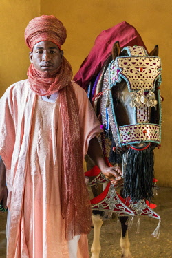 NGR1040 Nigeria, Kano State, Kano. The groom and horse in the stables of a dignitary related to the Emir of Kano.