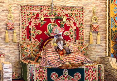 NGR1054 Nigeria, Kano State, Kano. The Emir of Kano sits cross-legged in his palace reception hall where he meets members of the Hausa community who come to pay him their respects.